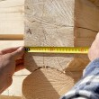 Stock Photo: Carpenter measures wooden logs