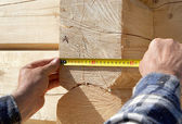 Carpenter measures wooden logs — Stock Photo