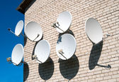 Seven satellite dish on the white wall — Stock Photo