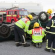 Fire and Rescue service staff at car crash training - Stock Photo
