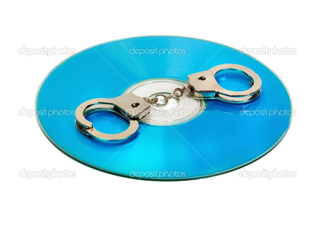 Pair of handcuffs on a CD computer isolated on white background — Stock Photo #8949982