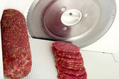 Slicer slices salami — Zdjęcie stockowe