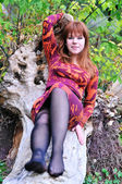 Redheaded girl resting in forest — Stock Photo