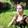 Girl blowing on dandelions — Stock Photo