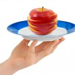 Hand with plate and chopped apple — Stock Photo