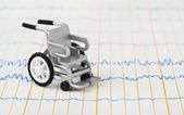 Toy wheelchair on ecg — Stock Photo
