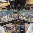 Stock Photo: Pilots in plane cockpit and city