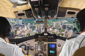 Pilots in the plane cockpit and city — Stock Photo