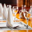 Glasses and plates on table in restaurant — Stock Photo #9700435
