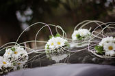Wedding flowers on the hood — Stock Photo