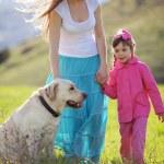 Happy family walking with dog — Stock Photo