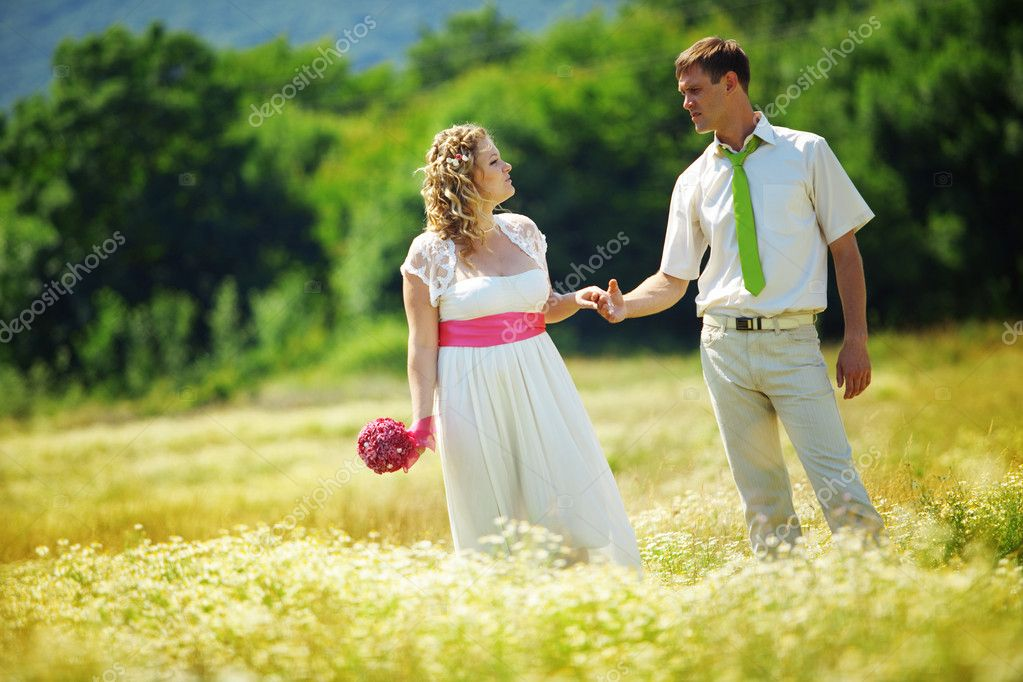 Wedding couple walking outdoor in field — Stock Photo #10346453