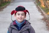 Cute little boy head in a funny hat outdoor in autumn — Stock Photo