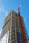 Lifting crane and high building under construction — Stock Photo