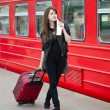 Young woman with luggage is waiting a train - Stok fotoğraf