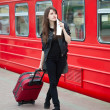 Young woman with luggage is waiting a train -  