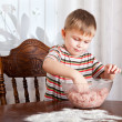 A boy is mixing mincemeat in a bowl - Stock Photo