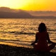 A woman is sitting in the lotus position on the beach — Stok fotoğraf