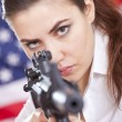 Woman with machine gun aiming — Stock Photo