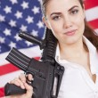 Stock Photo: Patriotic woman with gun over american flag