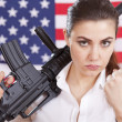 Woman with machine gun threatening - Stock Photo