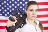 Woman with machine gun over american flag — Stock Photo