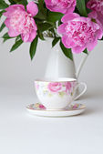 Teacup and pink peonies — Stock Photo