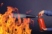 Man with extinguisher fighting a fire — Stockfoto