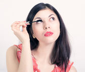 Portrait of pretty young woman applying mascara using lash brush — Stock Photo