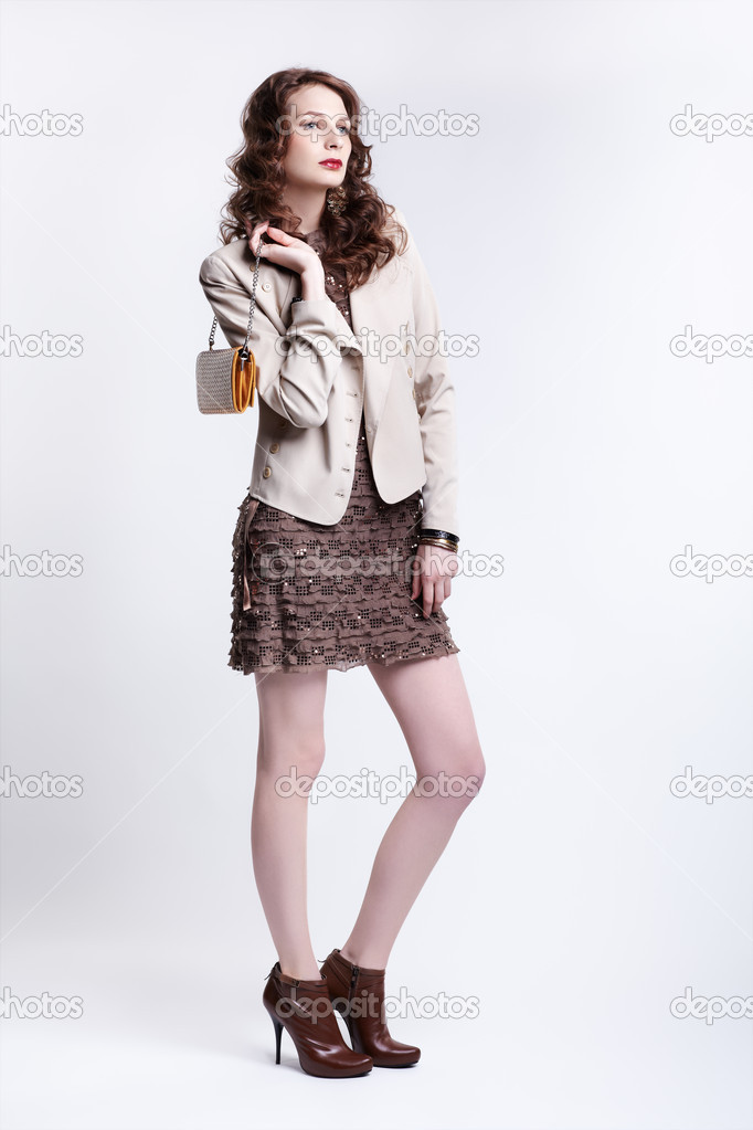 Portrait of beautiful young brunette woman in dress, jacket and boots with clutch in hand  Stock Photo #10206918