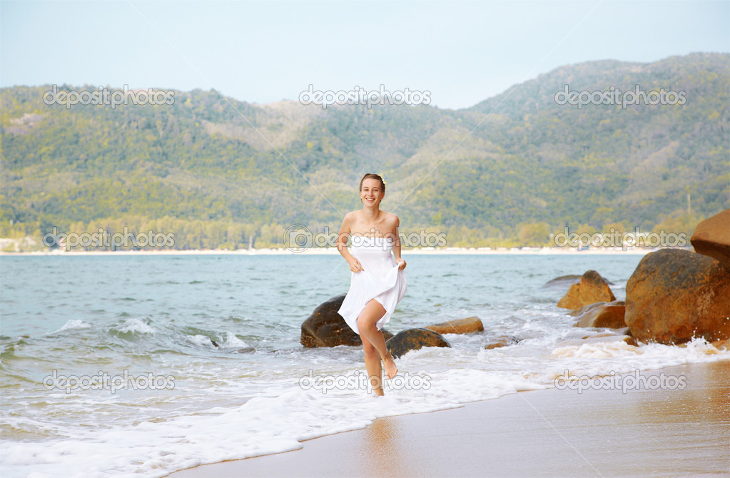 Outdoor portrait of young beautiful girl in white cotton clothes running in azure waves of of Phuket island, Thailand — Stock Photo #8330243