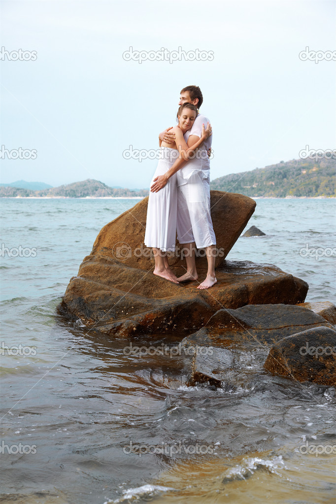 Outdoor portrait of young romantic couple embracing on stone among azure waters of Phuket island, Thailand — Stock Photo #8330548