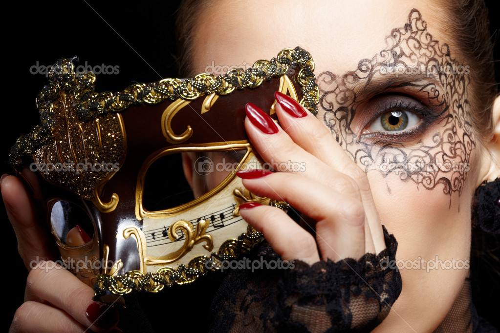 Close-up portrait of beautiful brunette woman with facial body art hiding half of her face with carnival venetian mask — Stok fotoğraf #8386391
