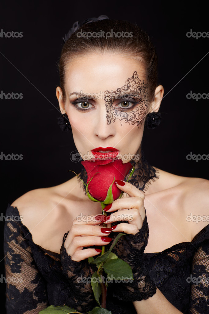 Portrait of beautiful brunette woman with facial bodyart in black lacy dress and gloves with red rose flower in hand — Stock Photo #8386529