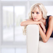Blond girl on sofa — Photo