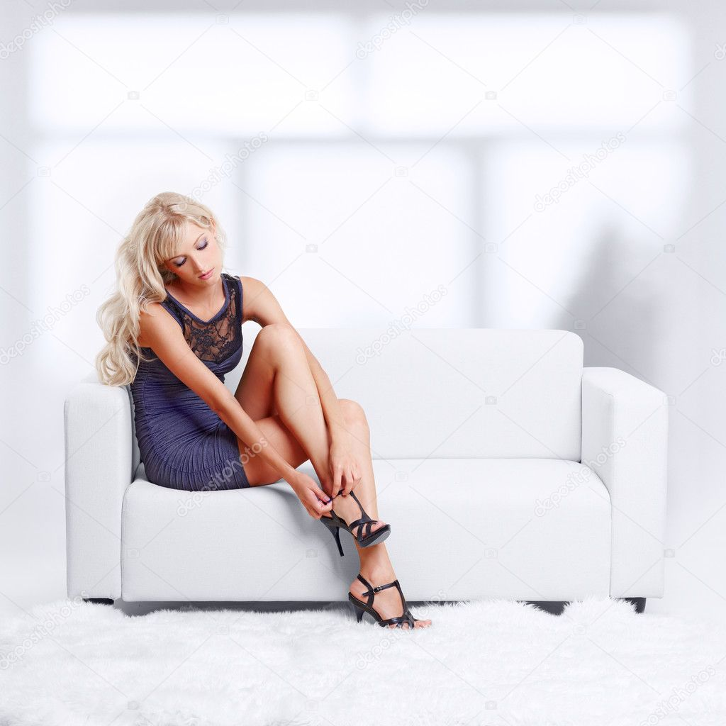 Full-length portrait of beautiful young blond woman on couch checking court shoe fastener  Stock Photo #8628593