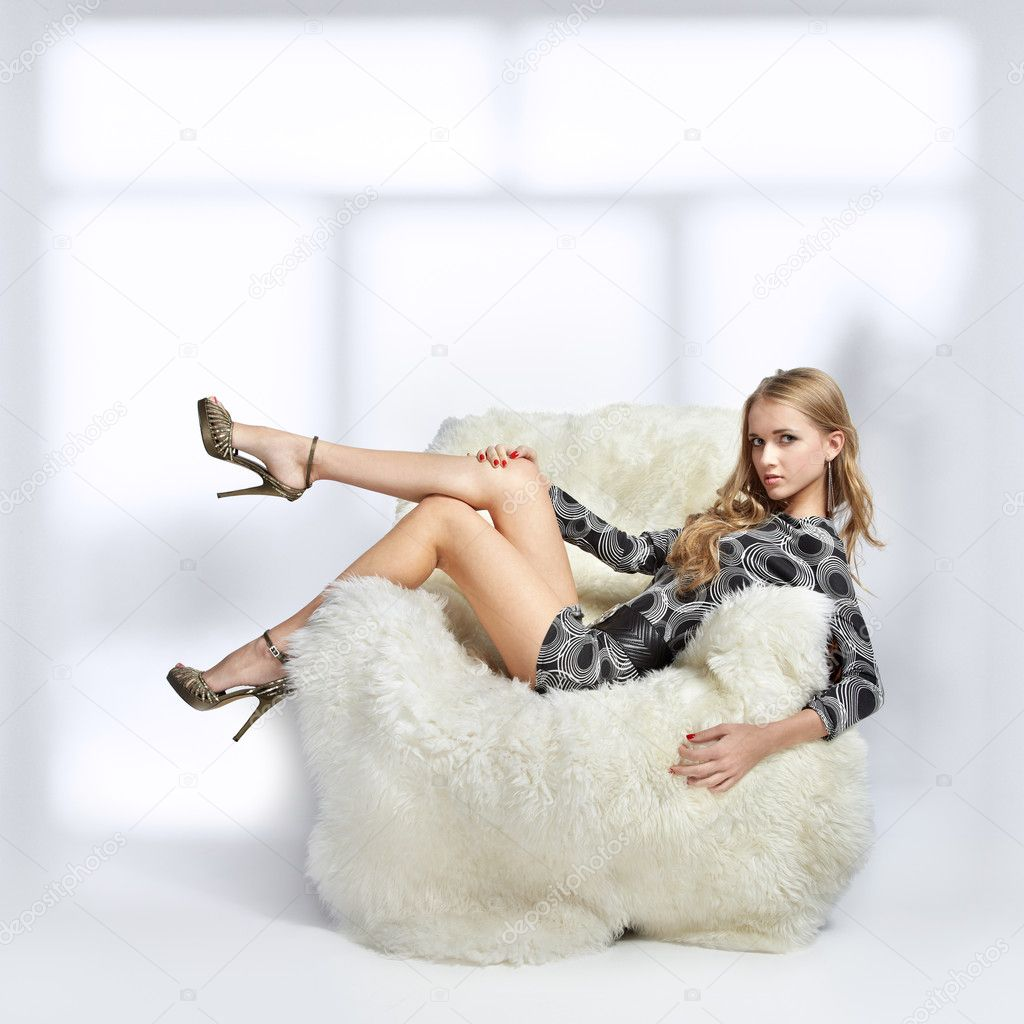 Portrait of beautiful blonde blue-eyed girl sitting in big furry arm-chair — Stock Photo #8629366