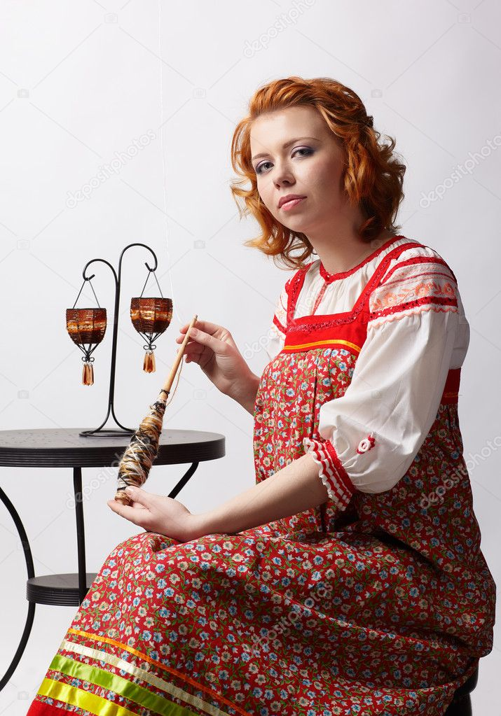 Portrait of beautiful slavonic redhead girl in traditional russian folk dress with distaff — Stock Photo #8741337