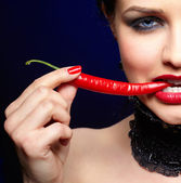 Beautiful brunette woman with red chilli pepper — Stock Photo