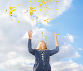 Young woman throwing leaves in the air — Stock Photo