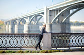 Beautiful woman with bridge on the background — Stock Photo