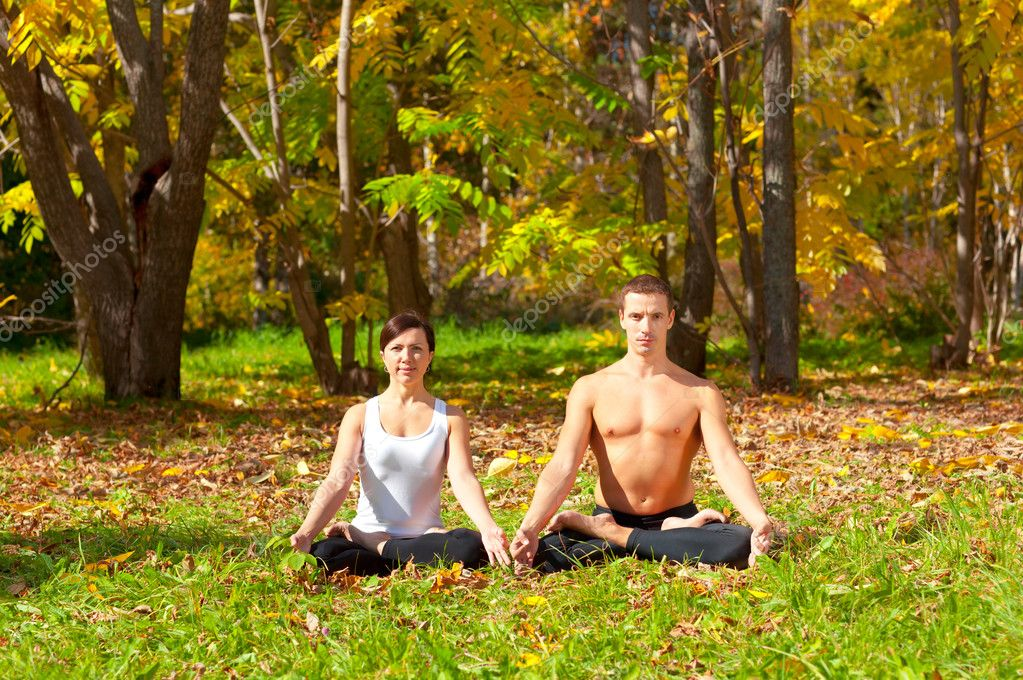 An attractive  man and woman practice Yoga padmasana pose in forest  Stock Photo #8800636