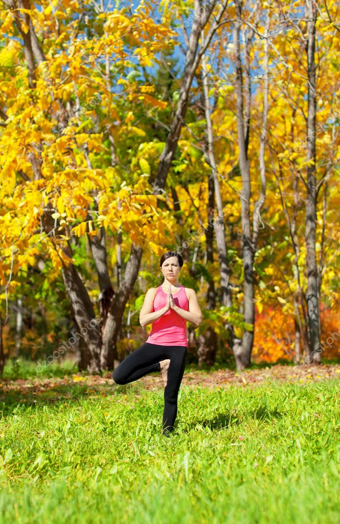 Woman Exercises in the autumn forest yoga Vrikshasana Tree Pose — Stock Photo #8800660