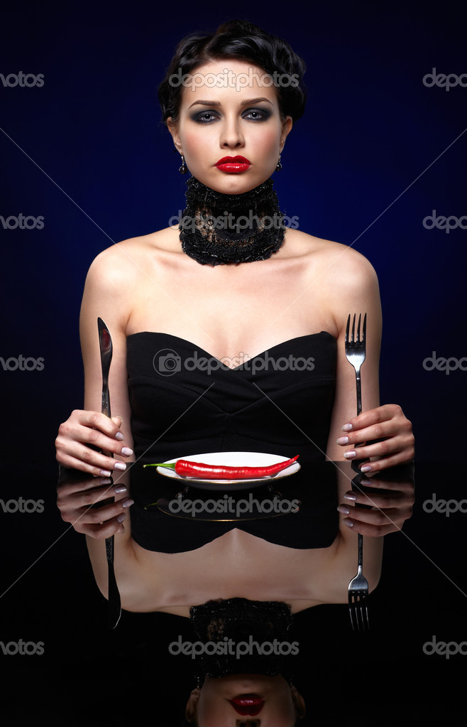 Portrait of beautiful brunette girl posing with fork, knife and single red hot spicy chilli pepper on white plate — Stock Photo #8801140