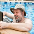 Man in pool with laptop — Stockfoto