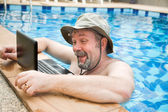Man in pool with laptop — Foto Stock