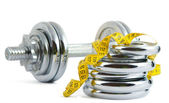 Dumbbell with a measuring tape — Photo