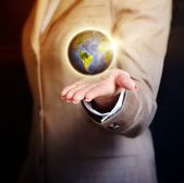 Business woman holding earth globe in her hand — Stockfoto