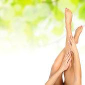 Vrouwelijke benen worden gemasseerd over groen — Stockfoto