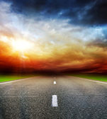Road in field over stormy dark cloudy sky — Stock Photo